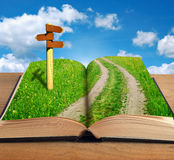 Magic book with road inside and signpost. On sky background stock photography