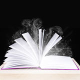 Magic book on a wooden table. Magical book on a black background royalty free stock images