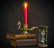 Magic books hourglass and candle Stock Photos