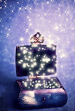 Magic box. A fantasy magic box with lights over lilac blue background with stars Royalty Free Stock Image