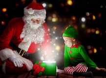 Magic box. Cute little girl and Santa Claus opening a magic gift box Stock Photo