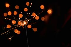 Magic burning sparkler. Dark background with blurred lights of Christmas garland. Copy space on the right.