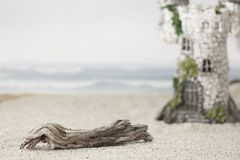 A magic castle at the beach. A piece of driftwood on a sandy beach with a fantasy castle and waves crashing in the background Royalty Free Stock Photography