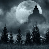 Magic castle silhouette over full moon at mysterious night. Fantasy background with pine tree forest under dramatic cloudy sky stock image