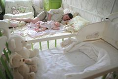 Magic in the children`s room. dad and son are sleeping. Dad and son are sleeping The kid is sitting on the floor in a bright room. Toys in the background. a royalty free stock image