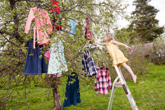 Magic choice of dresses. Little girl standing before the tree with dresses hanging on branches Stock Image