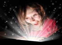 Magic Christmas. Beautiful young girl opens a Christmas magic gift stock photo
