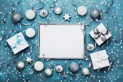Magic christmas background. Frame with xmas decoration, gift box, confetti and silver sequins on vintage blue table top view. Flat lay. Party mockup or festive Royalty Free Stock Image