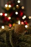 Magic christmas candle. Magic christmas mood with burning candle and glittering christmas tree lights Royalty Free Stock Photos