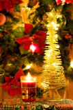 Magic Christmas candle and golden tree. Magic Christmas night celebration with festive red candle and golden lights tree Stock Image