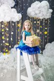 Girl in a studio with a gold stars decor Stock Photography