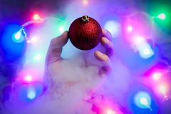 Magic christmas concept. A strange levitated Christmas ornament flies away from a man`s hand. Christmas garland lights at background with steam around royalty free stock photos