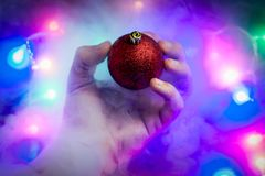 Magic christmas concept. A strange levitated Christmas ornament flies away from a man`s hand. Christmas garland lights at background with steam around stock image
