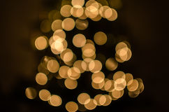 Magic holidays christmas defocused gold bright lights, bubbles and glitters in shape of christmas tree bokeh soft blur background royalty free stock photo