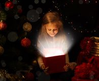 The magic of Christmas. Little girl opens a magical gift on the Christmas tree. The magic of Christmas. A little girl opens a magical gift on the Christmas tree stock photo