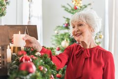 Elegant senior lady is preparing for New Year. Magic of Christmas. Positive old woman is holding candle and expressing gladness. She is decorating her house with stock photos
