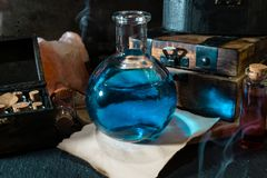Magic concept. Blue Potion in bottle and wooden box. Magic concept. Blue potion in bottle, candles, wooden box and craft paper. Magical background stock image