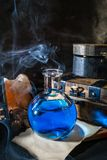 Magic concept. Blue potion in glass bottle. Magic concept. Blue potion in bottle, candle, old wooden boxes and smoke. Magical background stock image