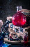 Magic concept. Red potion in bottle. Candles, wooden box. Magical background royalty free stock photography