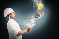Magic cooking recipes on the web. Chef looks stunned vegetables that come from tablet Stock Image
