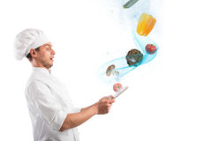 Magic cooking recipes on the web. Chef looks stunned vegetables that come from tablet Stock Photos