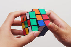 Magic cube. Colorful magic cube and hands, hints problem solving Royalty Free Stock Photo