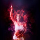 Magic dance. Of woman wearing a white tasselled bikini raising her arm in the air stock photo