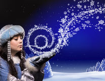 Magic of email in Christmas forest. A girl in a fairy dress conjures in Christmas forest. She breath makes snowflakes wich create sign of email and fly out Royalty Free Stock Image