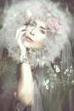 Magic fairy. Young beautiful  fantasy fairy woman with dandelion around her head on magic meadow Royalty Free Stock Photography
