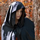 Magic fantasy atmosphere of woman with hood. Beautiful woman in fantasy land with red leafs stock photos