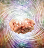 Magic. Female cupped hands emerging from twirling energy field with multicolored background and sparkles Stock Images