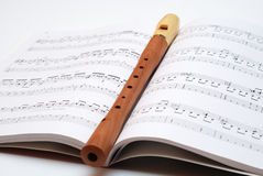 Magic flute. One recorder lying on the notes Stock Image