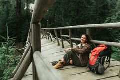 Cheerful young woman sitting on wooden footbridge stock photo