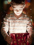 Magic gift. A surprised child opening and looking inside a magic gift Royalty Free Stock Photography