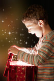 Magic gift. A surprised child opening and looking inside a magic gift Stock Image