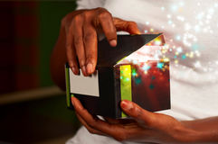 Magic gift box. African American woman opening a magic gift box Royalty Free Stock Photography