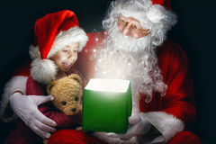 Magic gift box. Cute little girl and Santa Claus opening a magic gift box Royalty Free Stock Image