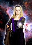 Magic girl. In mystical dress with glass ball and light over starry background Stock Photo