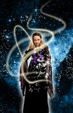 Magic girl. Blond girl in beautiful gothic dress with magic rays of light and stars Stock Photo