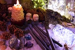 Black candles, cones, nature elements and shining bottle on table stock photo