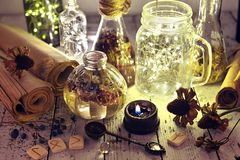 Lighting bottles with runes, seeds, herbs and old manuscripts on table royalty free stock image