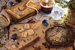 Open diary book with runes, dried herbs and tarot cards on table stock images