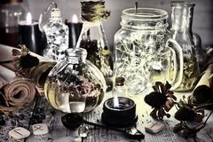 Shining bottles, spoon, old roots and parchments on witch table royalty free stock photography