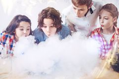 Group of children blowing on fume during chemistry experiment Stock Photos