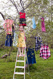 Magic harvest of dresses. Little girl standing before the tree with dresses hanging on branches Royalty Free Stock Image