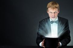 Magic hat. Image of male magician holding hat with magic light and looking at camera Royalty Free Stock Image