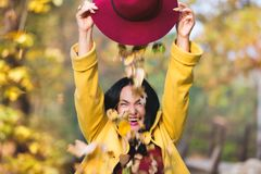 Magic hat with autumn leaves. Outdoor portrait of a pretty young woman enjoys in autumn park. sunset time, selective focus royalty free stock photos