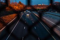 Magic Hour, sunset over highway through chainlink fence. Driving Home Magic Hour Sunset Urban highway looking through chainlink fence. Abstract and artistic Stock Photos