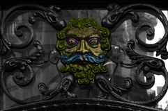 The magic iron face. Shot in black and white and painted in color, detail on the sculpture on the facade of the iron door of this historic building representing Royalty Free Stock Photos