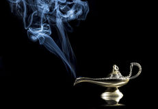 Magic lamp on black background from the story of Aladdin with Genie appearing in blue smoke concept for wishing, luck and magic Stock Photo